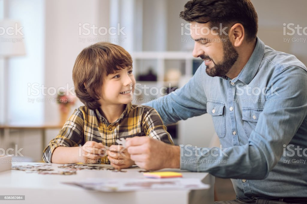 Happy smiling boy looking at his father stock photo