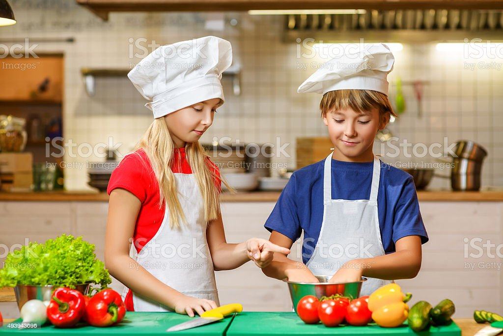Happy smiling Chef boy and girl preparing healthy food at stock photo