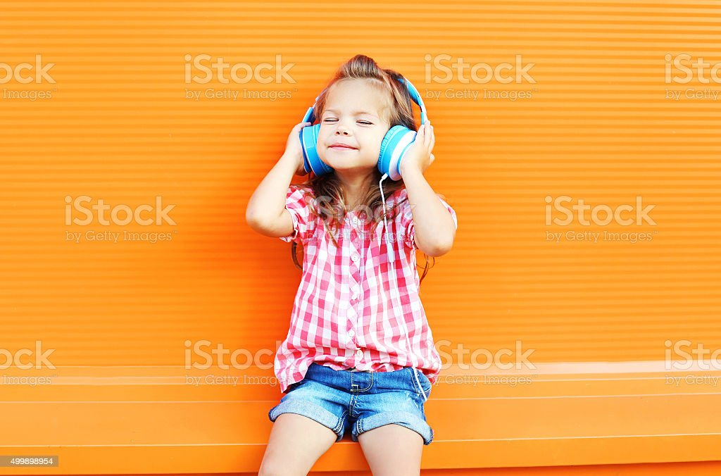 Happy smiling child enjoys listens to music in headphones stock photo