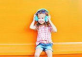 Happy smiling child listens to music in headphones over colorful