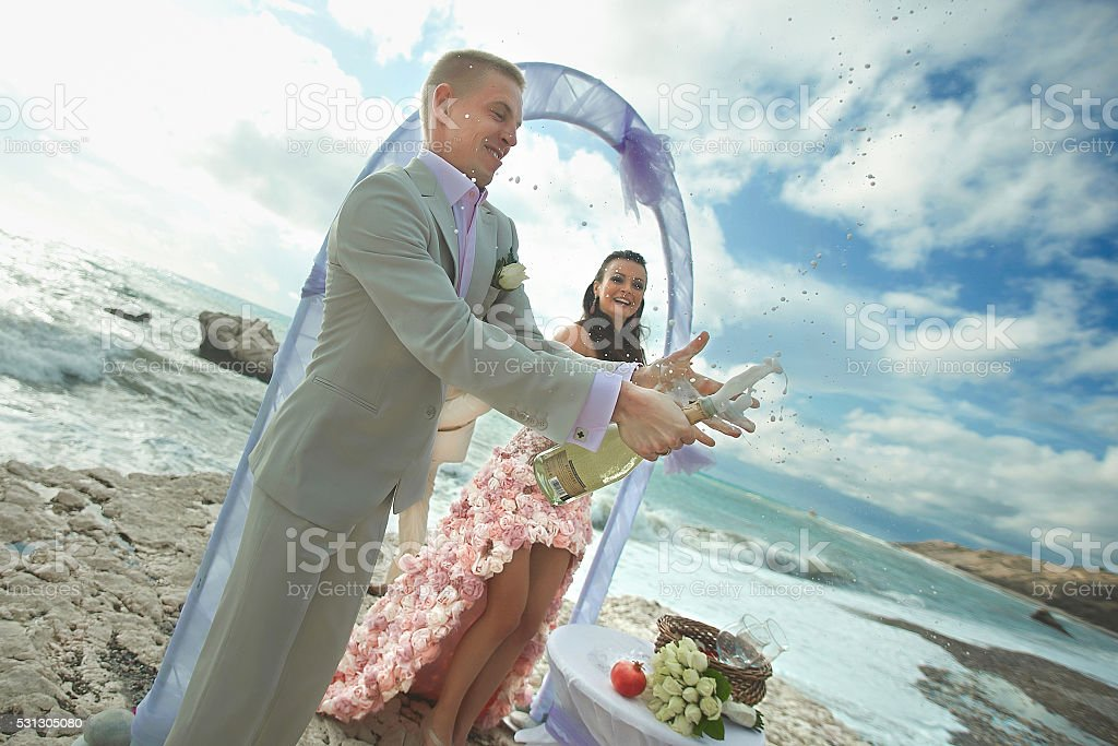 Happy, smiling couple open bottle of champagne during wedding. stock photo