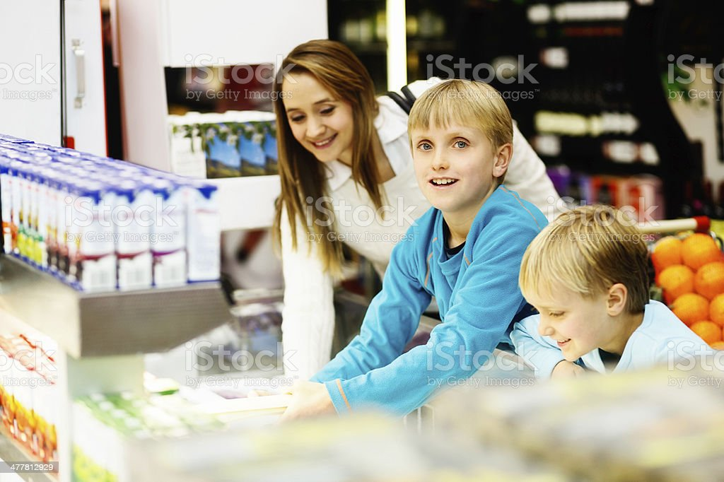 Happy, smiling family shopping for fresh juice in supermarket royalty-free stock photo