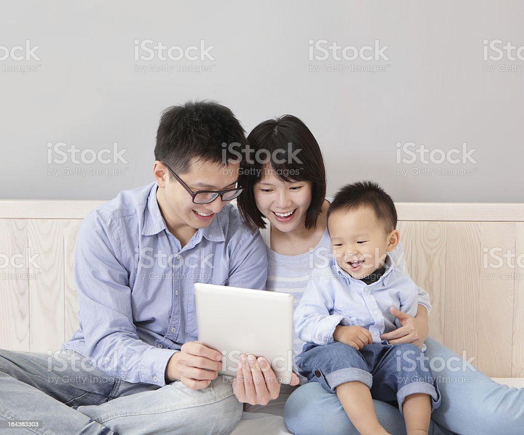 Happy, smiling family utilizing their tablet royalty-free stock photo