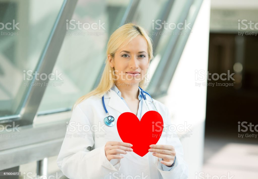 happy smiling female health care professional, woman family doctor cardiologist with stethoscope holding red heart stock photo