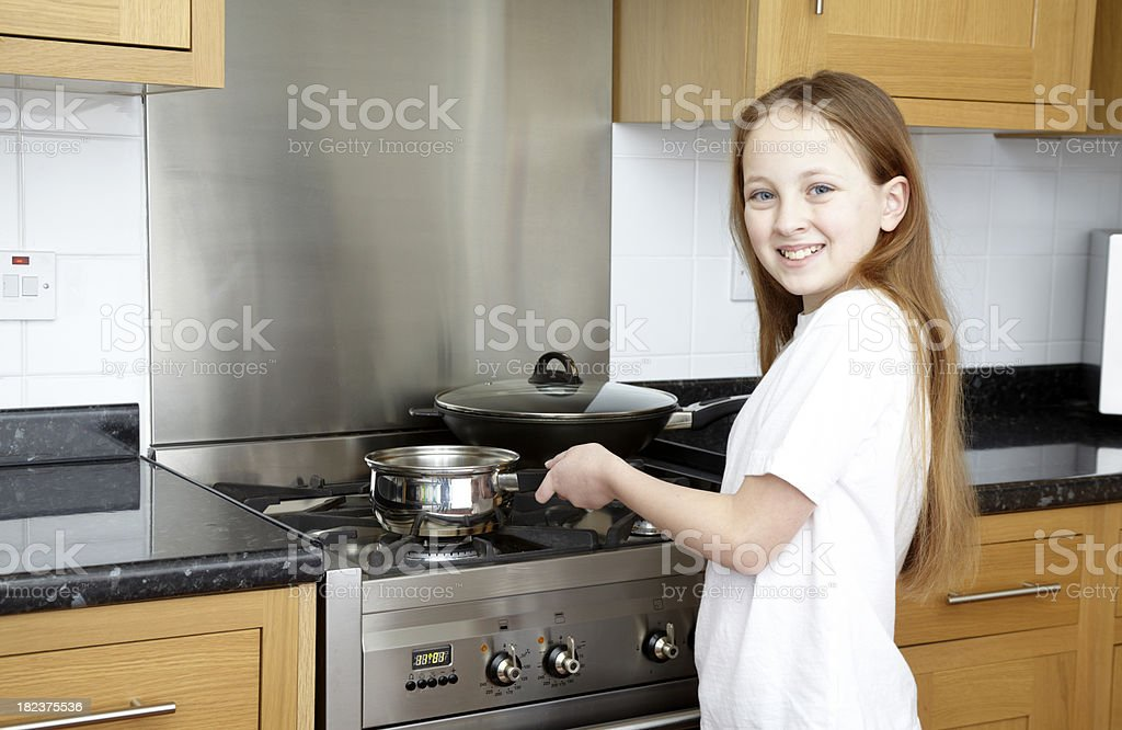 Happy Smiling Girl cooking with pan in kitchen royalty-free stock photo