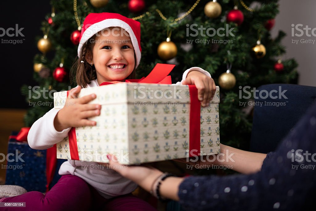 Happy little girl is receiving her present while sitting in front of...
