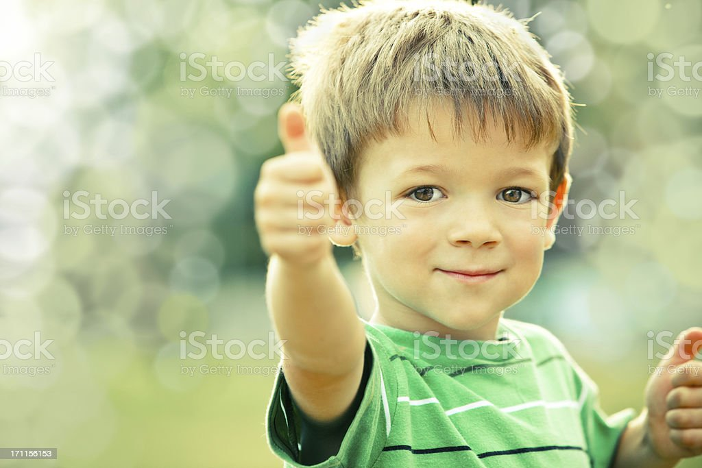 happy smiling kid outdoor doing OK portrait green tone royalty-free stock photo