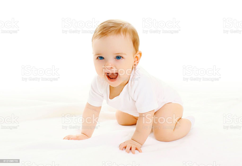 Happy smiling little baby crawls on a white background stock photo