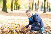 Happy smiling little boy playing with leaves