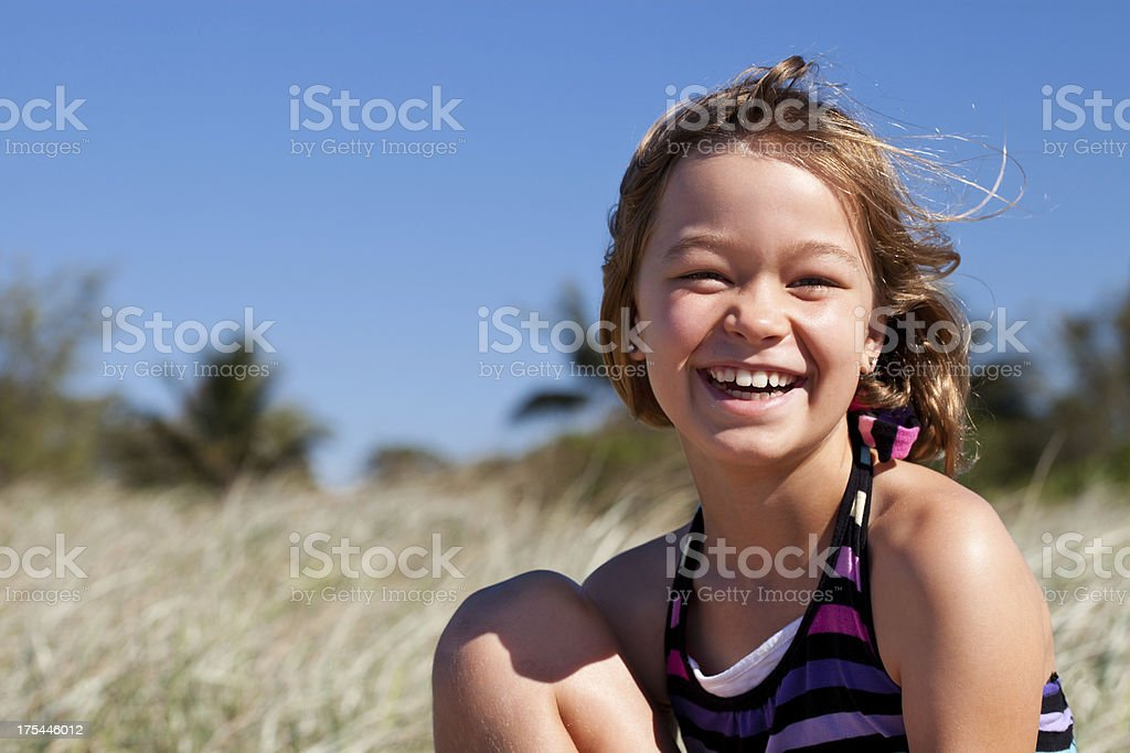 Happy smiling little girl at the beach in sunshine stock photo