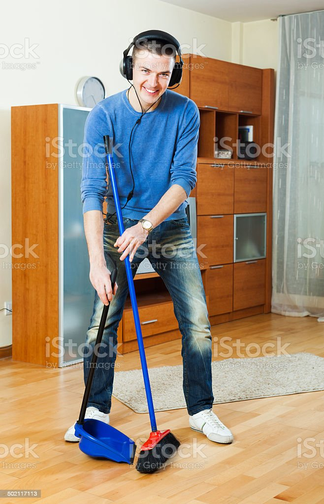 Happy smiling man sweeping floors in living room stock photo