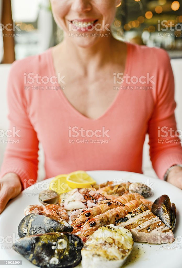 Happy Smiling Mature Woman with plate of grilled seafood royalty-free stock photo