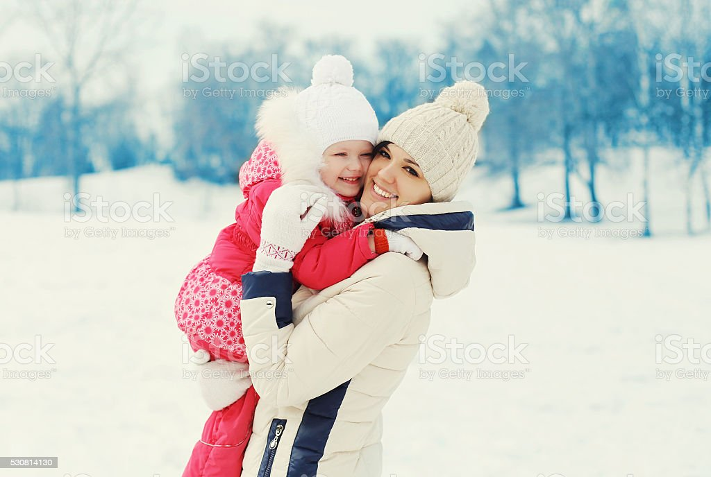 Happy smiling mother and child together in winter day stock photo