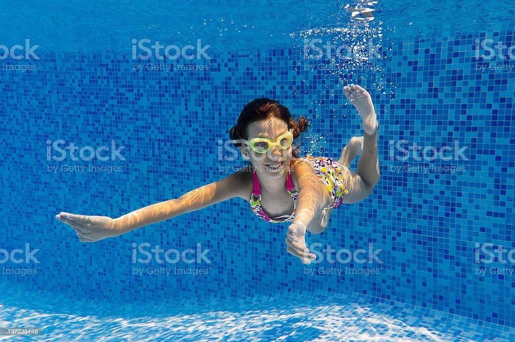 Happy smiling underwater child in swimming pool stock photo