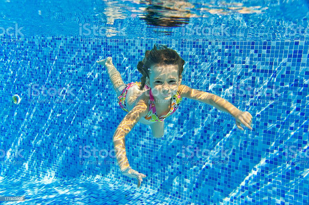 Happy smiling underwater child in swimming pool royalty-free stock photo