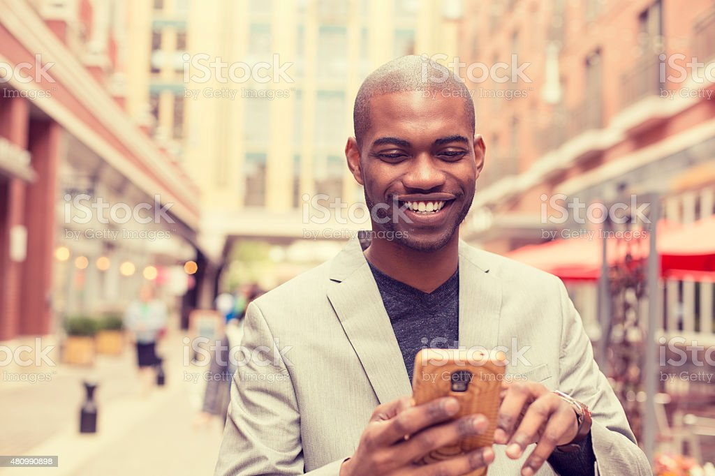 happy smiling urban professional man using smart phone stock photo