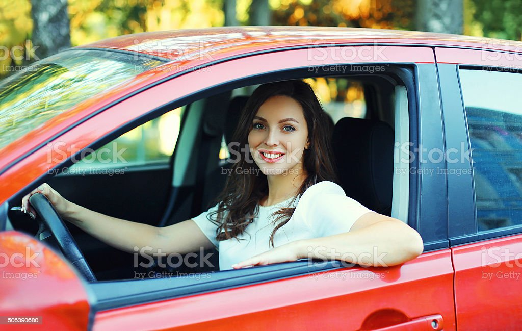 Happy smiling woman driver behind the wheel red car stock photo