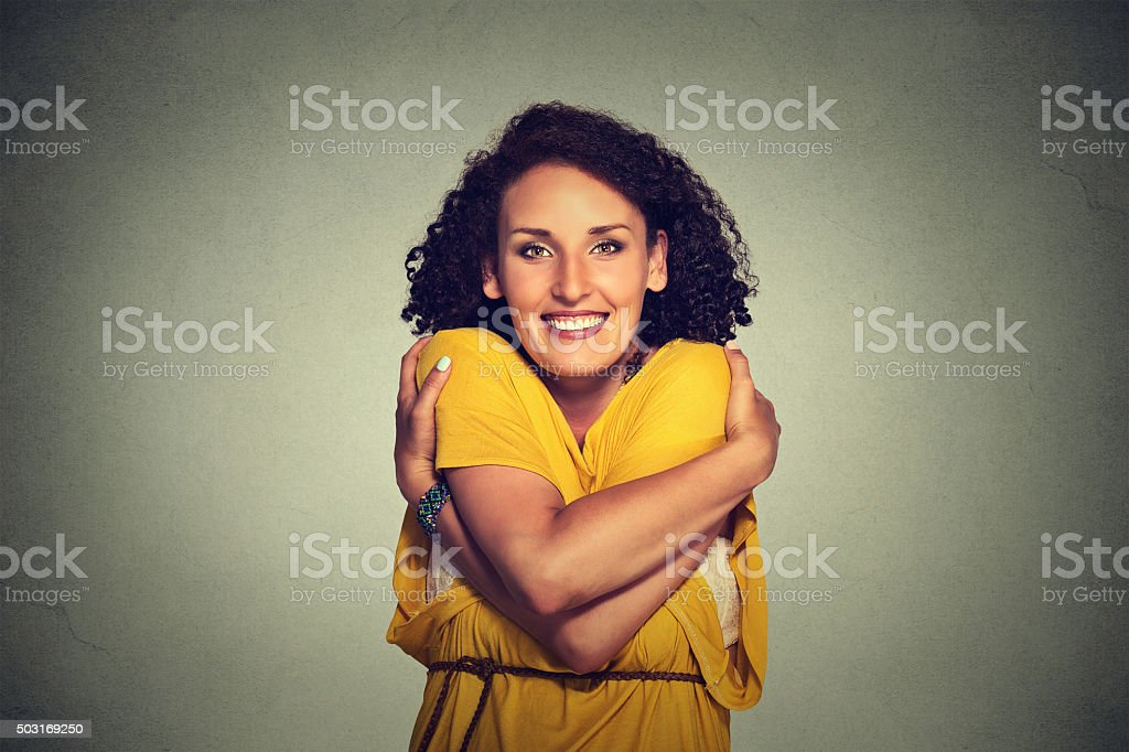 happy smiling woman holding hugging herself stock photo