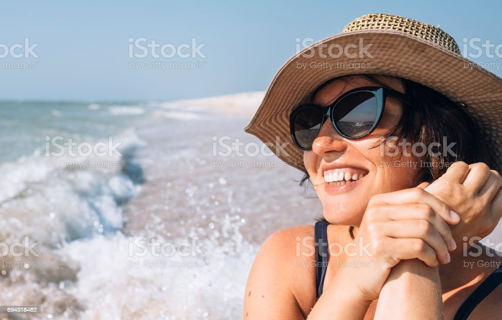 Happy smiling woman in straw hat on the sea beach stock photo
