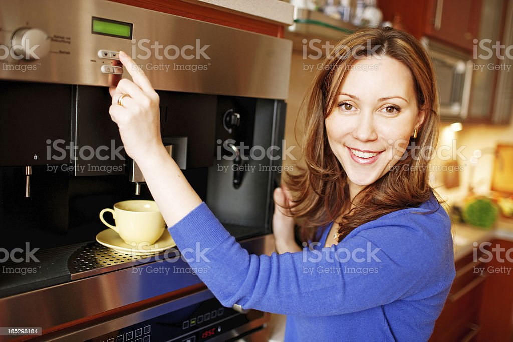Happy Smiling Woman making coffee in the kitchen stock photo