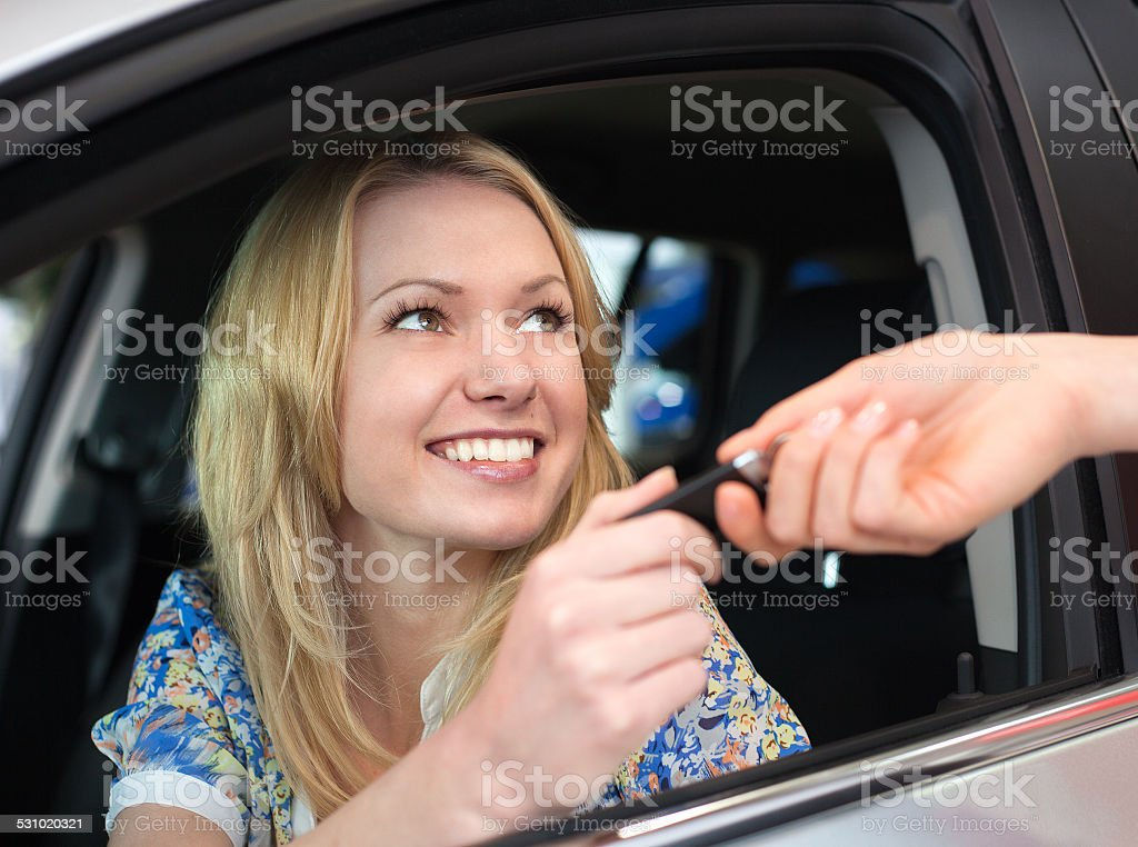 Happy smiling woman with car key in car stock photo