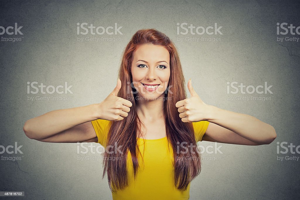 Happy smiling woman with thumbs up gesture stock photo