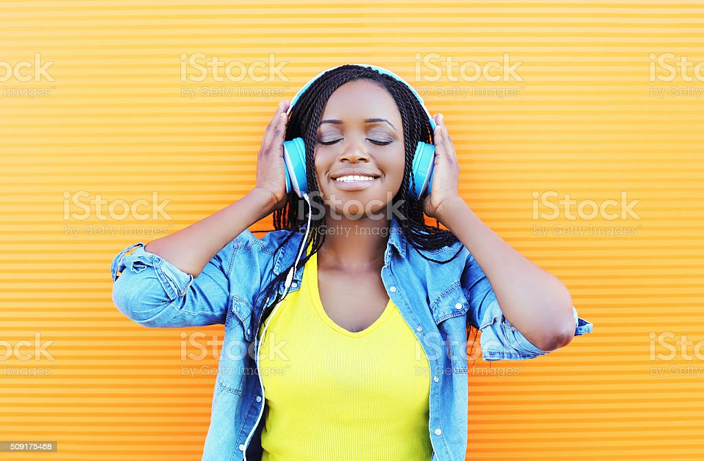 Happy smiling young african woman with headphones enjoying listens music stock photo