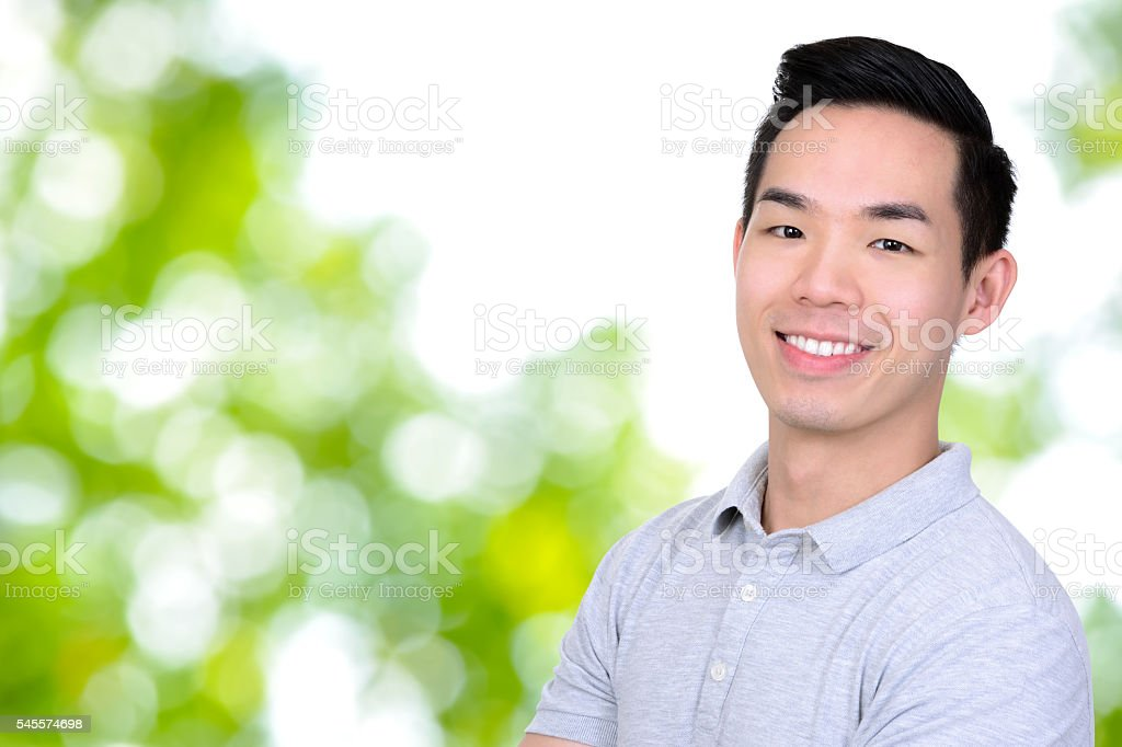 Happy smiling young Asian man on bokeh green abstract background stock photo