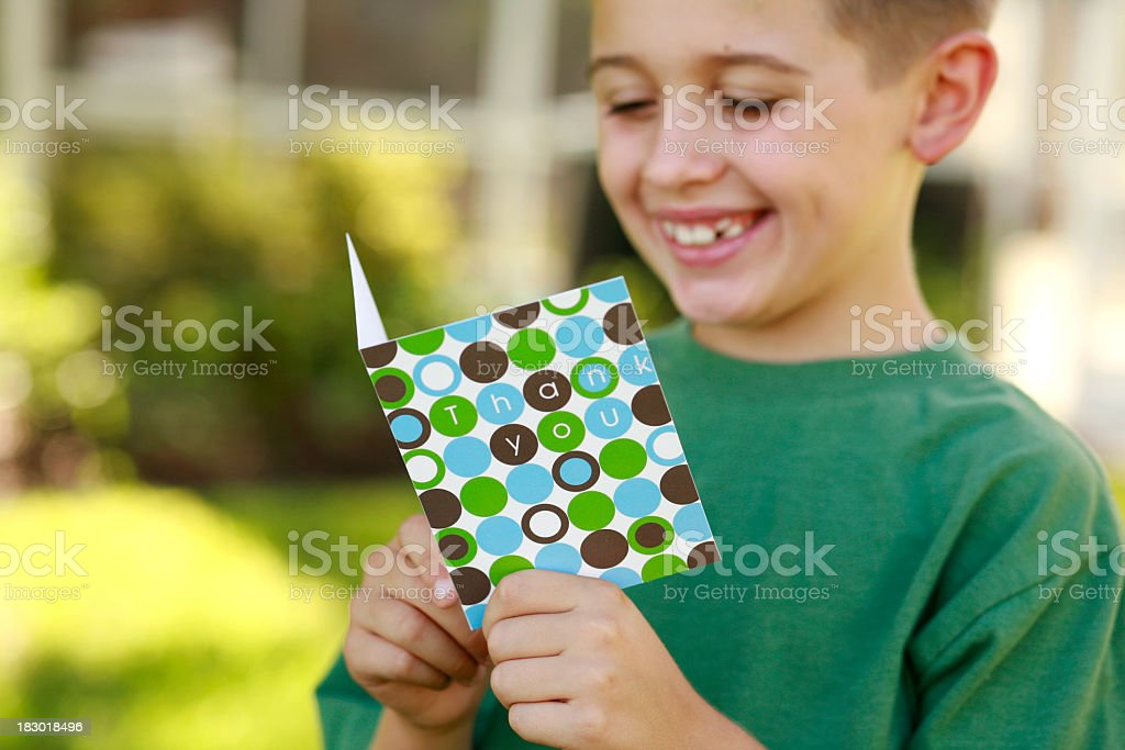 Happy smiling young boy reading a thank you card outdoors royalty-free stock photo