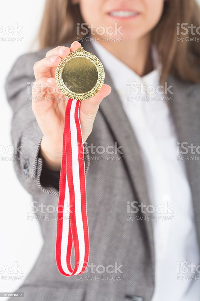 Happy smiling Young Businesswoman holds up her gold medal stock photo