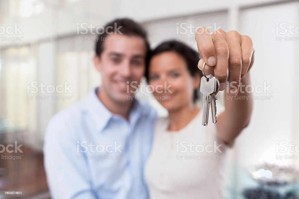 Happy smiling young couple showing keys of their new house stock photo