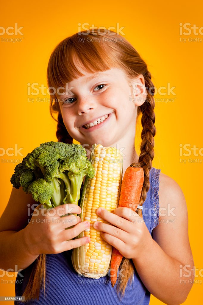 Happy, Smiling Young Girl Holding Broccoli, Corn, Carrot royalty-free stock photo