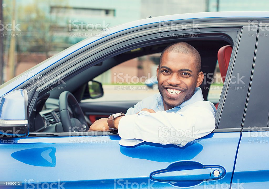 happy smiling young man buyer sitting in new car stock photo