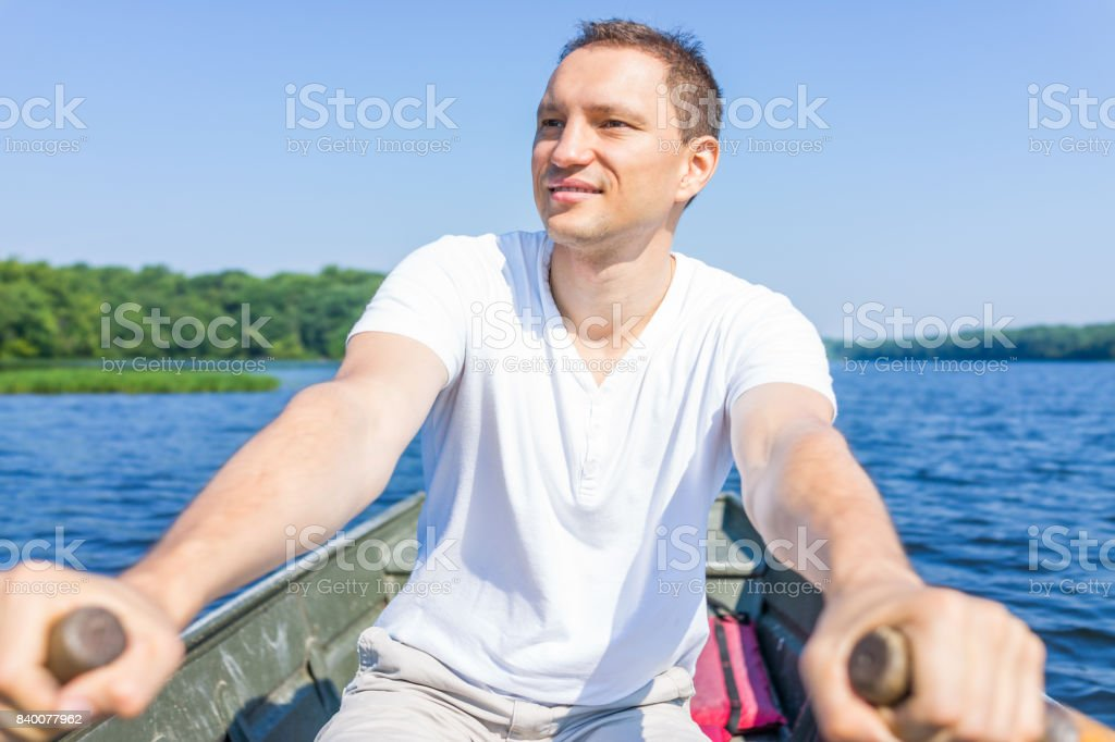 Happy smiling young man rowing boat on lake in Virginia during summer in white shirt stock photo
