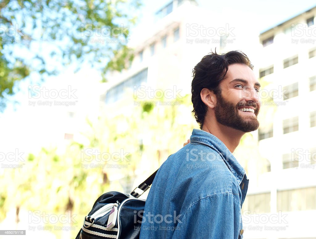 Happy smiling young man standing outdoors with travel bag stock photo