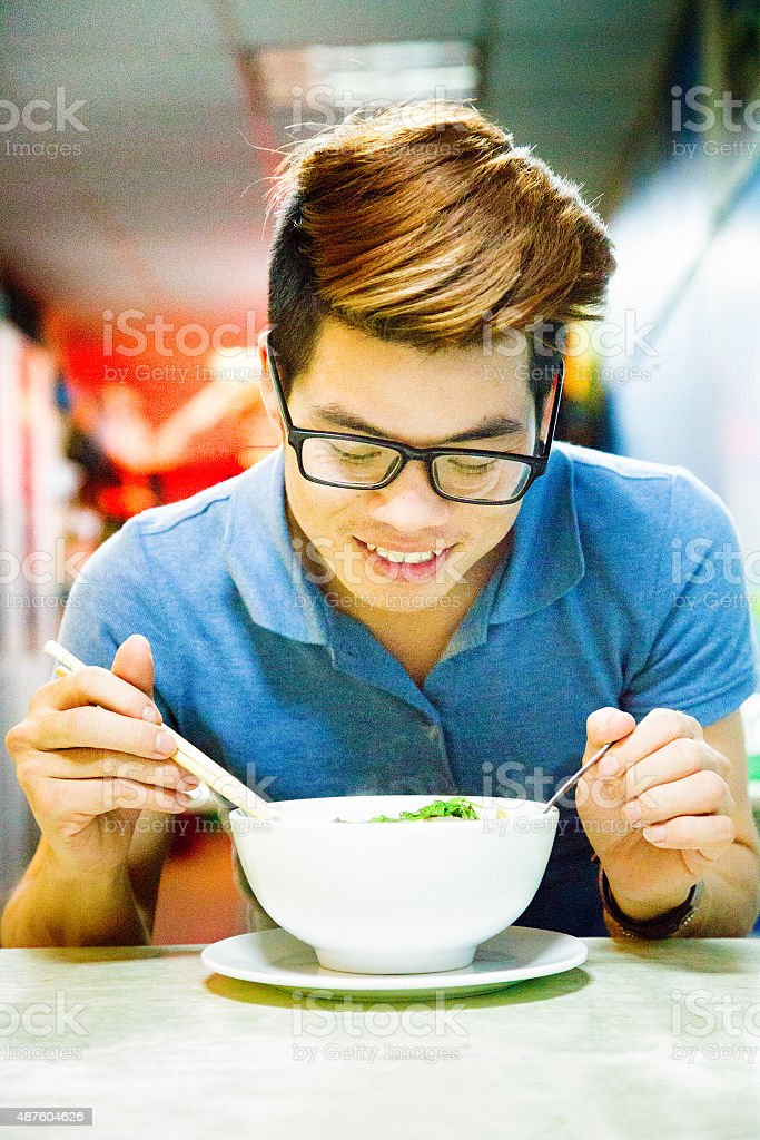 Happy smiling young Vietnamese man over bowl of Pho stock photo