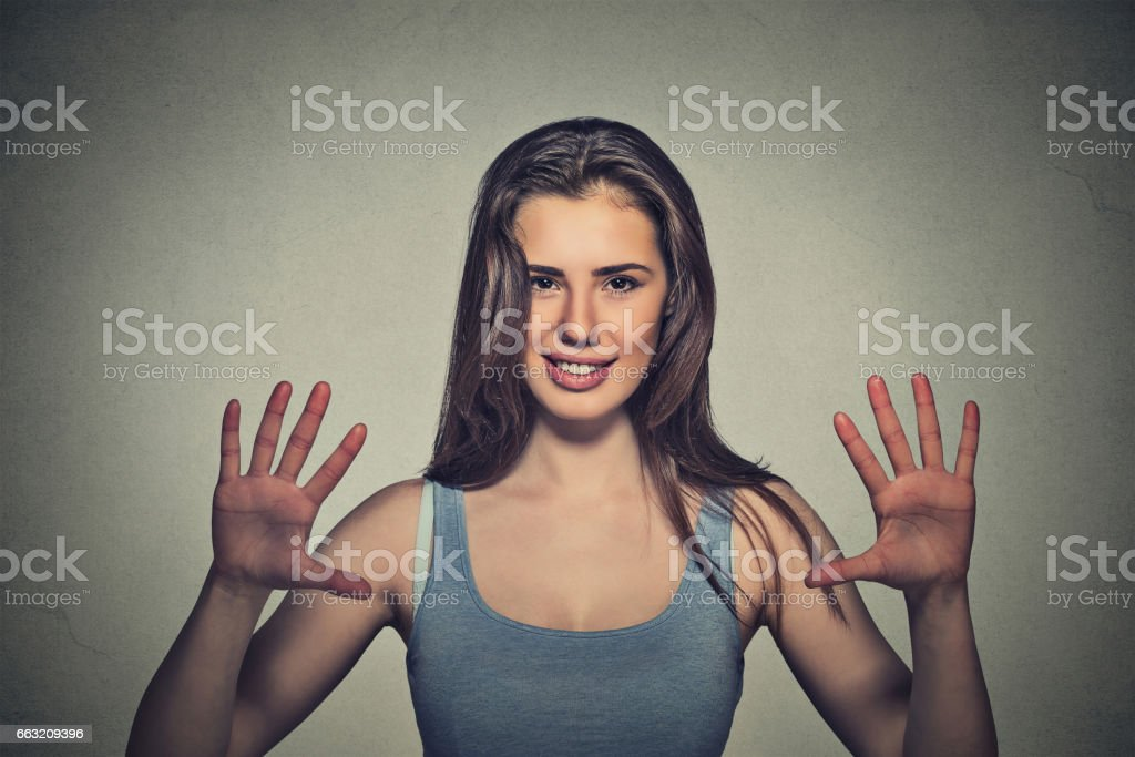 happy, smiling young woman making five times sign gesture stock photo