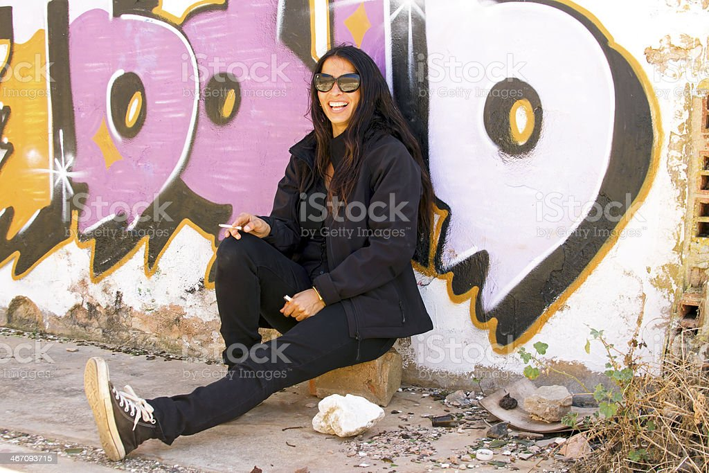 Happy smoking woman in front of a graffiti wall royalty-free stock photo