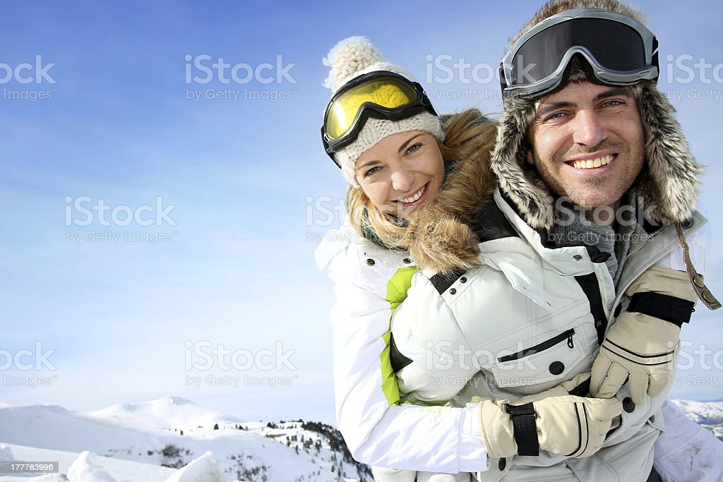 Happy snowboarder holding girl on his back stock photo