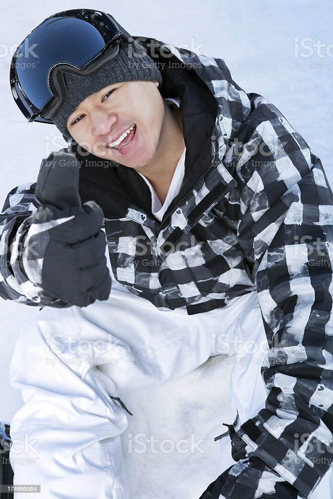 Happy snowboarder sitting on snow with thumbs up royalty-free stock photo