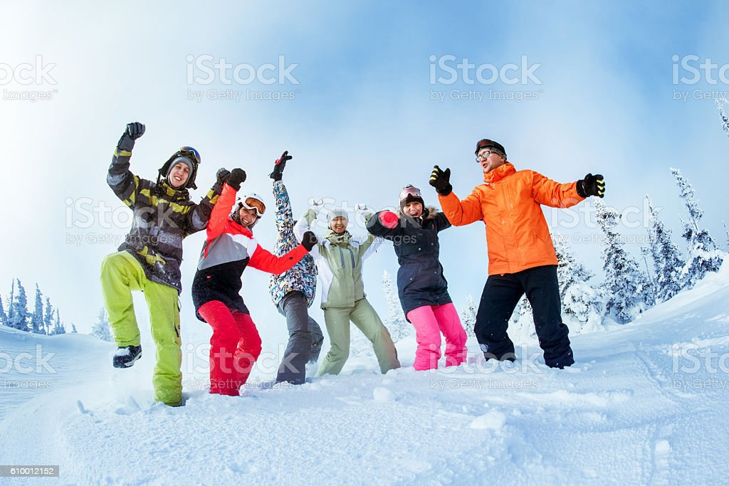 Happy snowboarders posing on blue sky backdrop in mountains stock photo