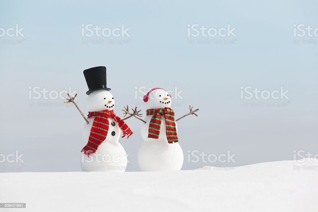 Happy Snowman Christmas Couple Wearing Top Hat, Ear Muffs, Scarves stock photo