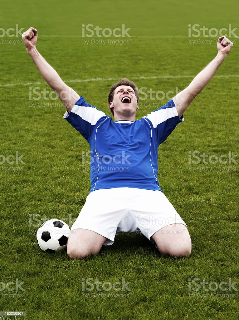 Happy soccer player celebrates victory with hands in the air royalty-free stock photo