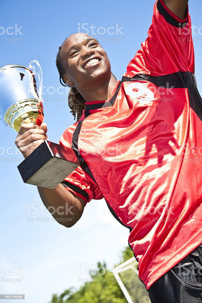 Happy Soccer Player With Championship Trophy Waving to Fans royalty-free stock photo