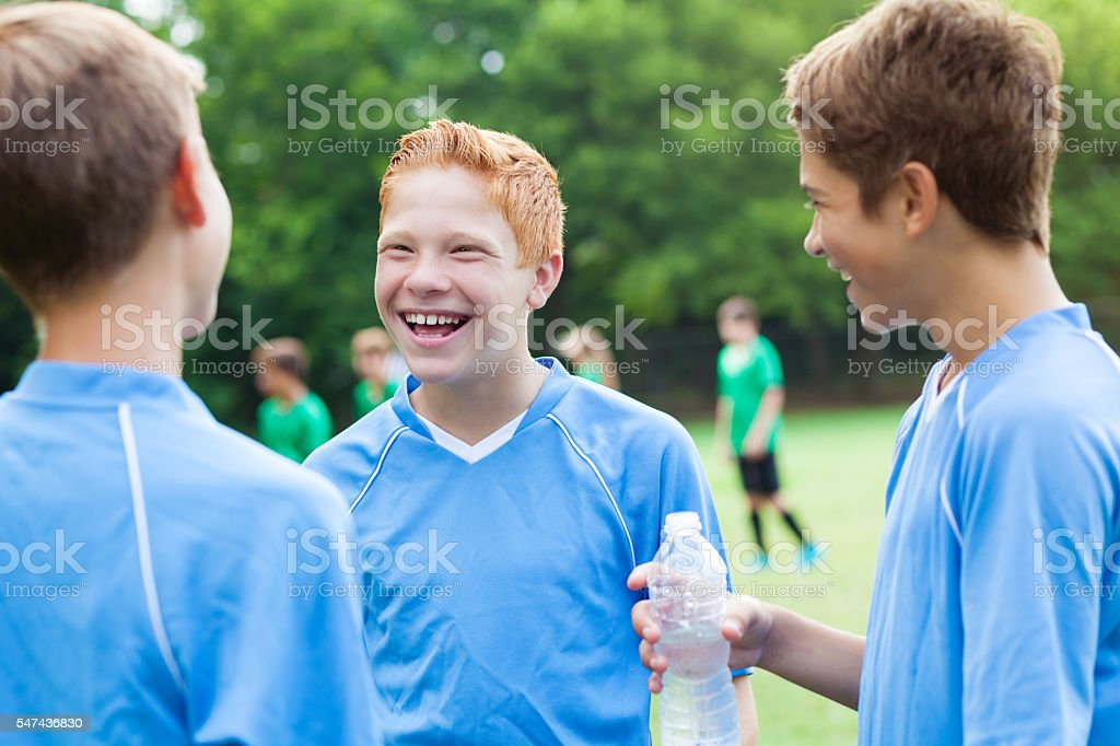 Happy soccer players taking a water break stock photo
