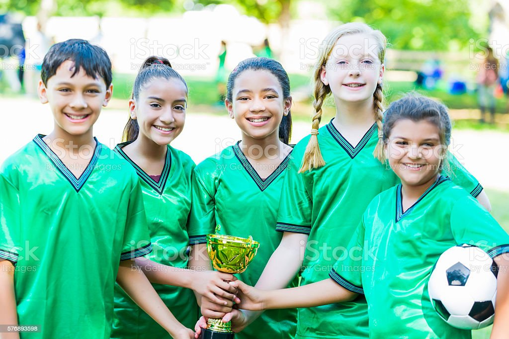 Happy soccer team holding trophy together stock photo