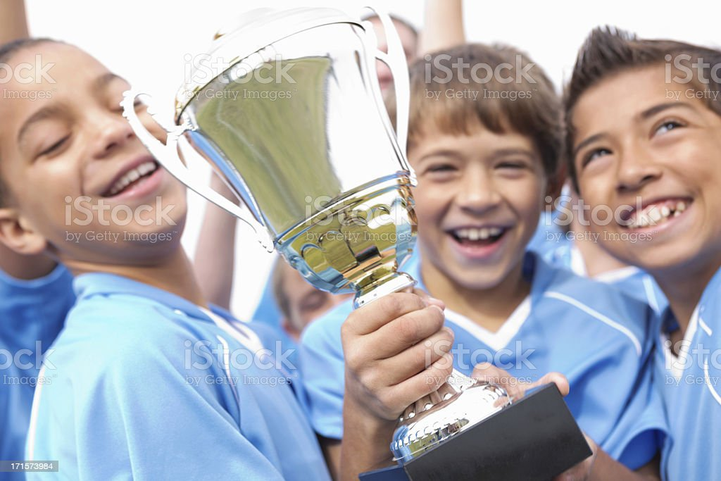 Happy soccer team players celebrating with winning trophy stock photo