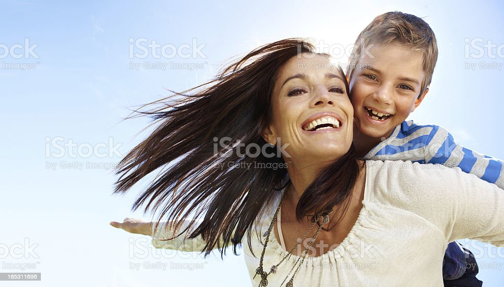 Happy son on smiling mother's back on a sunny day royalty-free stock photo