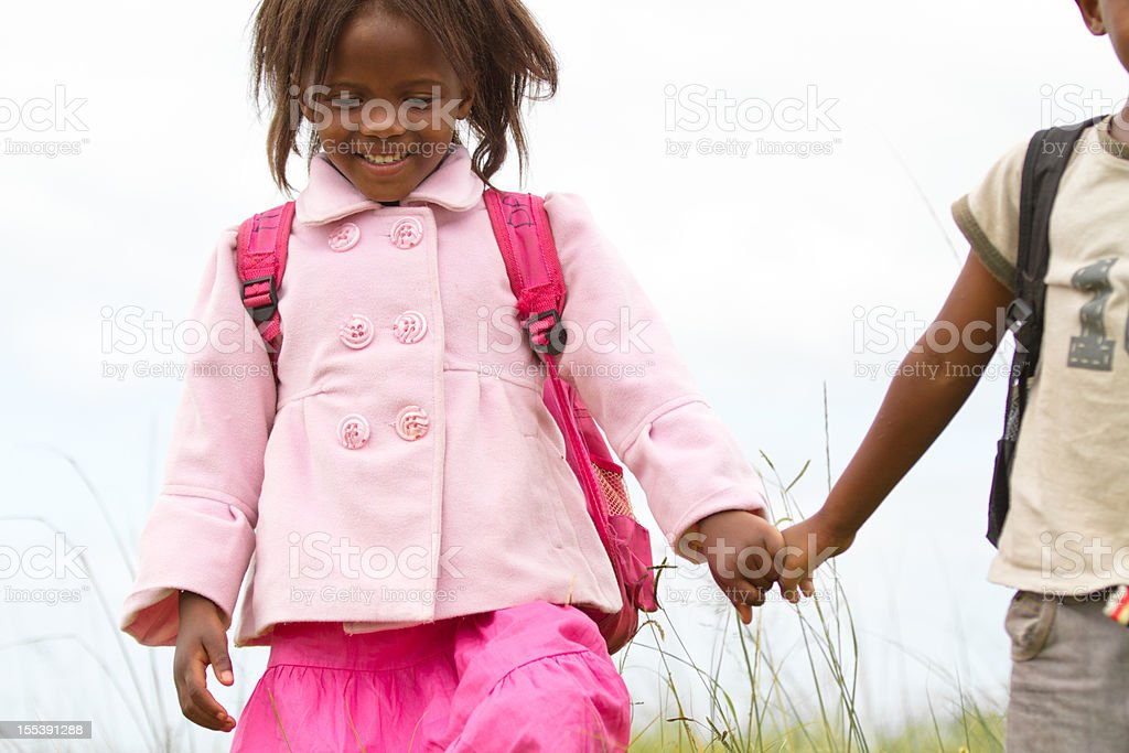 Happy South African girl smiling and holding her brothers hand stock photo