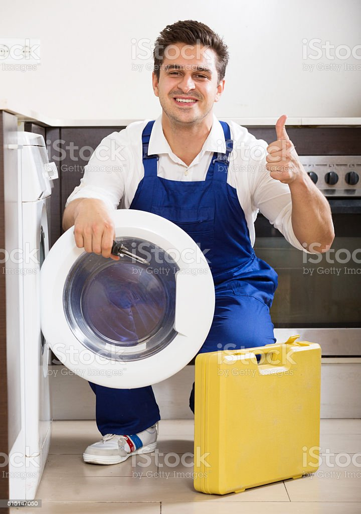 Happy specialist with tooling near washing machine stock photo